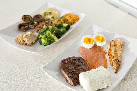 deliberation: animal versus plant proteins: one plate with beef, eggs, salmon, cheese and chicken grill and another with nuts, mushrooms, broccoli, lentil, hummus and quinoa Stock Photo