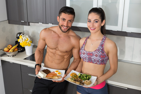 source: fit couple in the kitchen; animal versus plant proteins: one plate with beef, eggs, salmon, cheese and chicken grill and another with nuts, mushrooms, broccoli, lentil, hummus and quinoa Stock Photo
