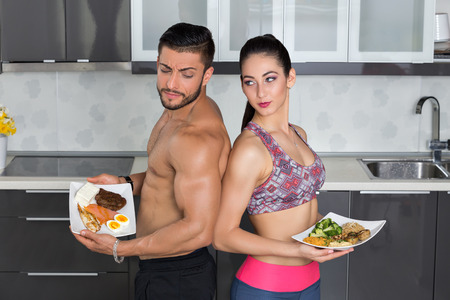 one animal: fit couple looking angry in the kitchen; animal versus plant proteins: one plate with beef, eggs, salmon, cheese and chicken grill and another with nuts, mushrooms, broccoli, lentil, hummus and quinoa