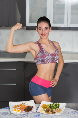 one animal: young fit woman in the kitchen, showing her biceps; animal versus plant proteins: one plate with beef, eggs, salmon, cheese and chicken grill and another with nuts, mushrooms, broccoli, lentil, hummus and quinoa Stock Photo