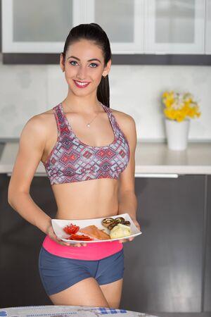 plato del buen comer: Mujer joven del ajuste en la cocina, preparando la comida sana: un plato con salmón, champiñones, patatas, tomate y pimiento rojo