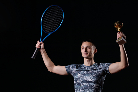 young professional tennis player holding a trophy, blue racket, black background Reklamní fotografie