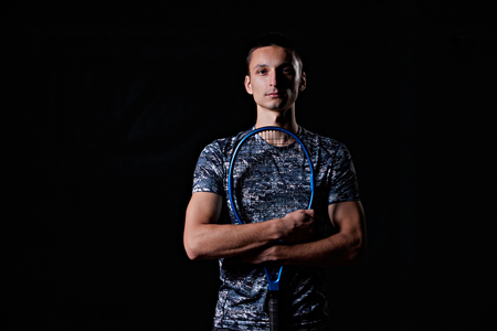 young professional tennis player holding a blue racket, on black background Reklamní fotografie