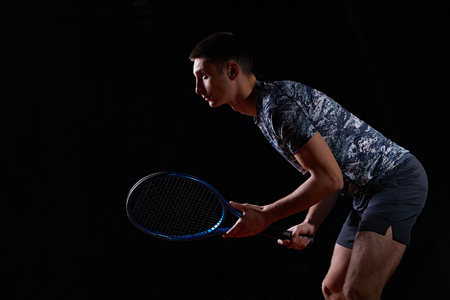 young professional tennis player holding a blue racket, on black background, waiting to return a serve Reklamní fotografie