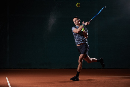 young professional tennis player with a blue racket hitting a forehand, black background, wet ball creating a splash Reklamní fotografie