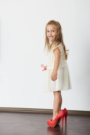 Happy little blonde girl trying mother's shoes, smiling, looking up