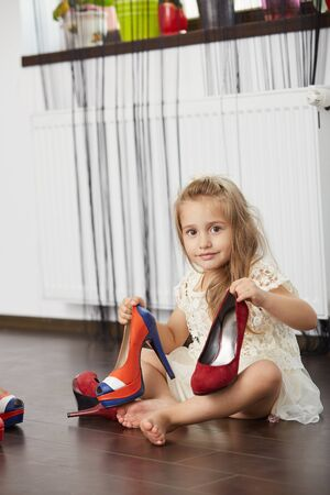 Happy little blonde girl trying mother's shoes, choosing from three pairs of high heels
