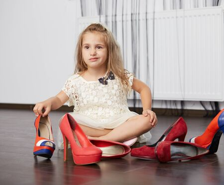 pretentious little blonde girl trying mother's shoes, choosing from three pairs of high heels