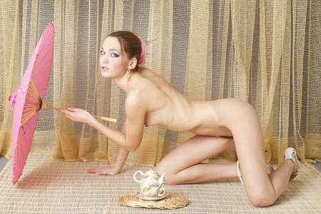 nude ass: A young woman with an umbrella and teapot Stock Photo