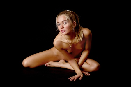 Naked blonde on black background.