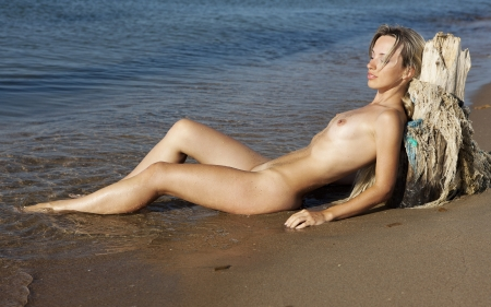 Beautiful nude girl. Naked young woman on the beach.