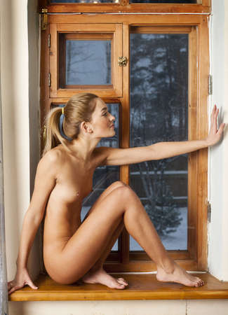 Naked girl on the windowsill  Portrait of nude babes  Stock Photo