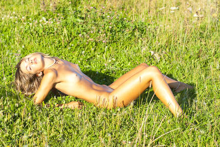 Naked girl sunbathes on a meadow  Stock Photo