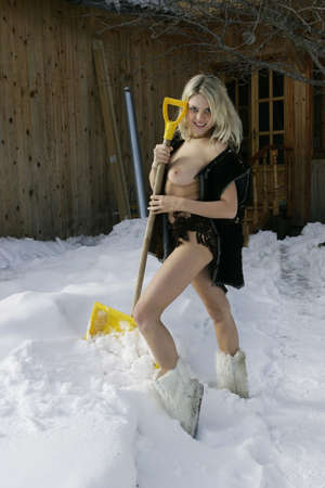 Nude blonde with a shovel the snow