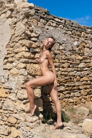 junge frau nackt: Nackte junge Frau in der N�he einer Steinmauer
