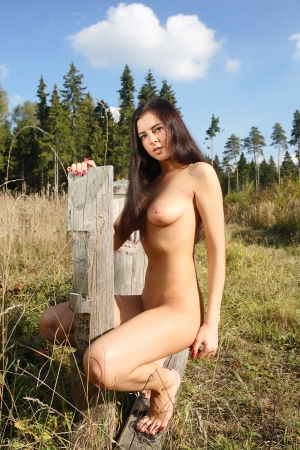 Young woman with beautiful breasts in the forest