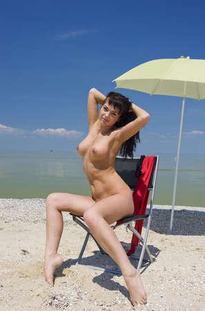 nue plage: Belle brune sur la plage sous un parapluie. Banque d'images