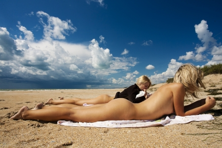 Two girls sunbathe on the beach