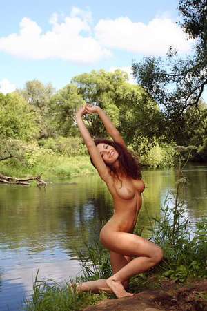Nude girl with big tits on the bank of the river forest  Stock Photo
