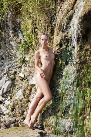 Nude girl on the beach near a small waterfall