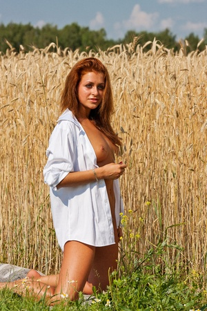Beautiful nude girl   Young naked woman on a field of rye  Reklamní fotografie