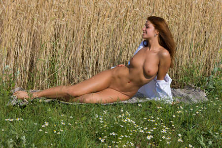 Young naked woman of rye. Nude girl in the field.
