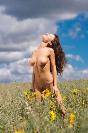 nude nature: Nude girl on a field of sunflowers. Portrait of a naked woman with beautiful boobs.