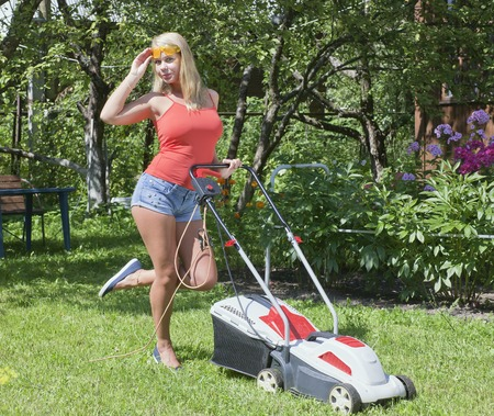Girl and lawn mower. Young woman in the garden.