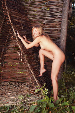 nude model: Nude girl in a wickiup. Portrait of a naked woman. Stock Photo