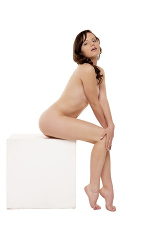 nude girl sitting: Nude girl sitting on a cube. Isolated on white background.