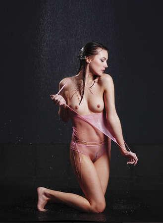 tetas: chica desnuda bajo la lluvia. Retrato de una mujer mojada.