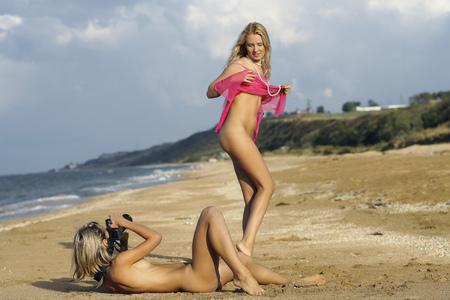 girls naked: Две голые девушки фотографируются на пляже.