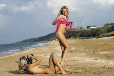 girls naked: Two naked girls are photographed on the beach.