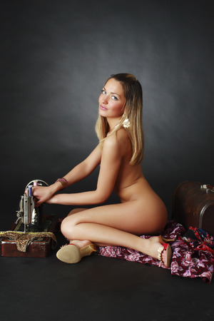 Naked girl: Beautiful naked girl near a sewing machine Stock Photo