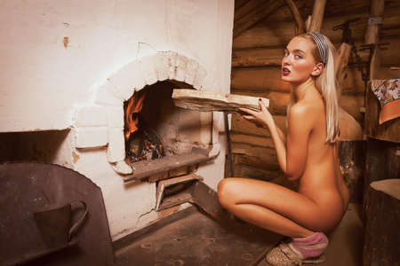 Naked beauty near the stove. photo