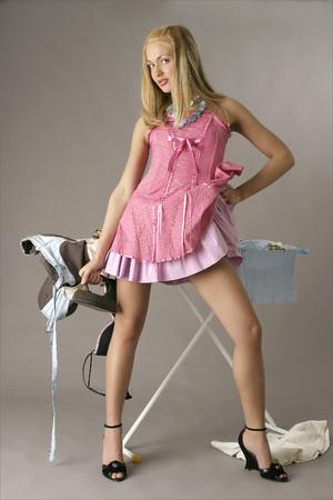 Pretty woman with iron. Stock Photo