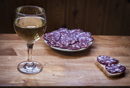 Wine Riesling in a glass and smoked sausage on a plate.