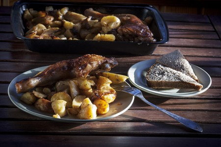 Chicken leg with fried potatoes. Stock Photo