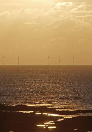 windfarm: Parques e�licos en alta mar a la puesta del sol  Foto de archivo