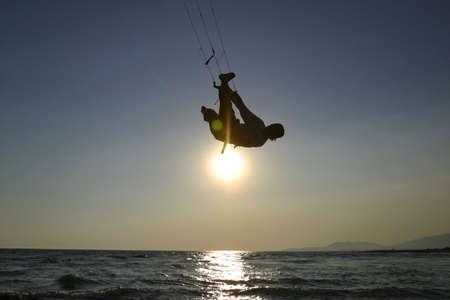 kitesurfer riding fast and jumpimg at sunset