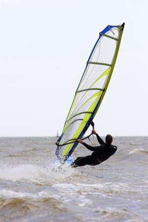 exhilarating: windsurfer sailing away form the beach