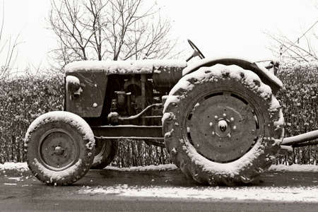 black and white photograph of classic old tractor in winter photo