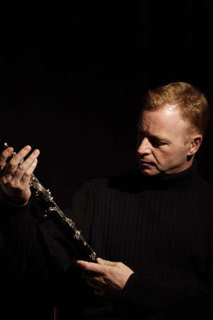 melodious: musician holding a clarinet isolated against black background Stock Photo