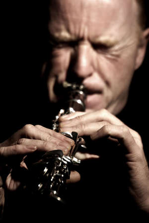 clarinete: M�sico tocando un clarinete aislados contra fondo negro  Foto de archivo
