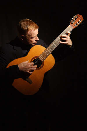 jamming: man playing a guitar isolated on black background Stock Photo