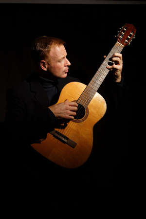 spanish guitar: man playing a guitar isolated on black background Stock Photo