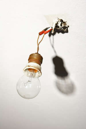 light bulb hanging from bare wires with shadow photo