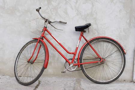 rust red: viejo retro bicicleta apoyan en la pared