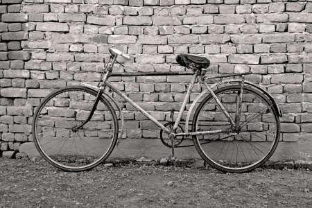 bicicleta retro: vieja bicicleta del retro que se inclina contra una pared