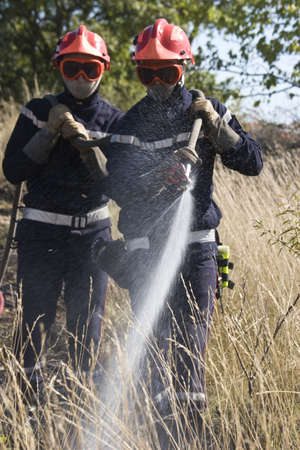 firemen team putting out bush fire Stock Photo